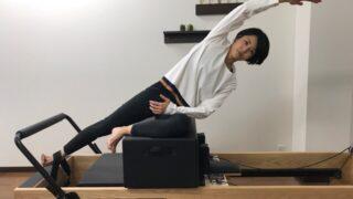 ピラティスリフォーマーでサイドリーチエクササイズをする女性
