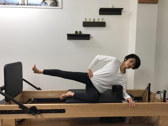 ピラティスリフォーマーでジャンプエクササイズをする女性