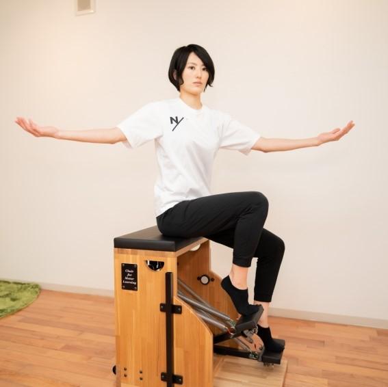 ピラティスチェアで足部のエクササイズをする女性の写真