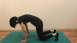 四つ這い姿勢で背骨を丸める女性