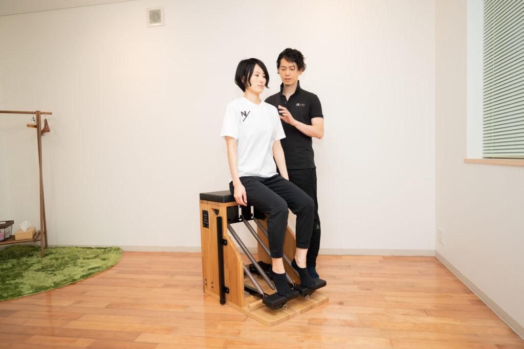 ピラティスチェアでエクササイズをする女性と男性インストラクター