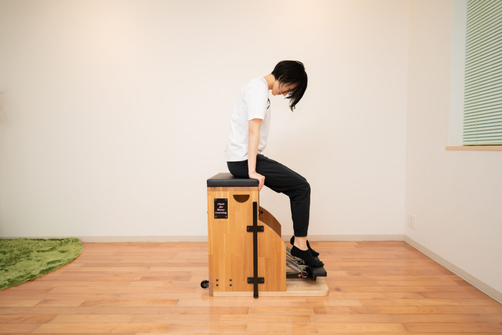 ピラティスチェアに座る女性