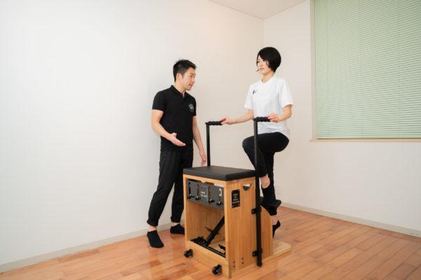 ピラティスチェアを使う女性と指導する男性トレーナー