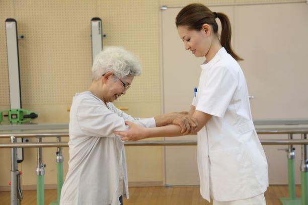 リハビリ室で歩行訓練に励む高齢女性