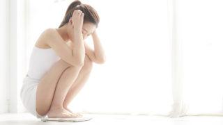 体重計に乗り思い悩む女性
